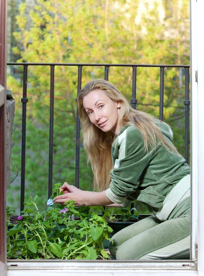 Die junge Frau landet Sämling auf einem Balkon. Porträt lizenzfreies stockfoto