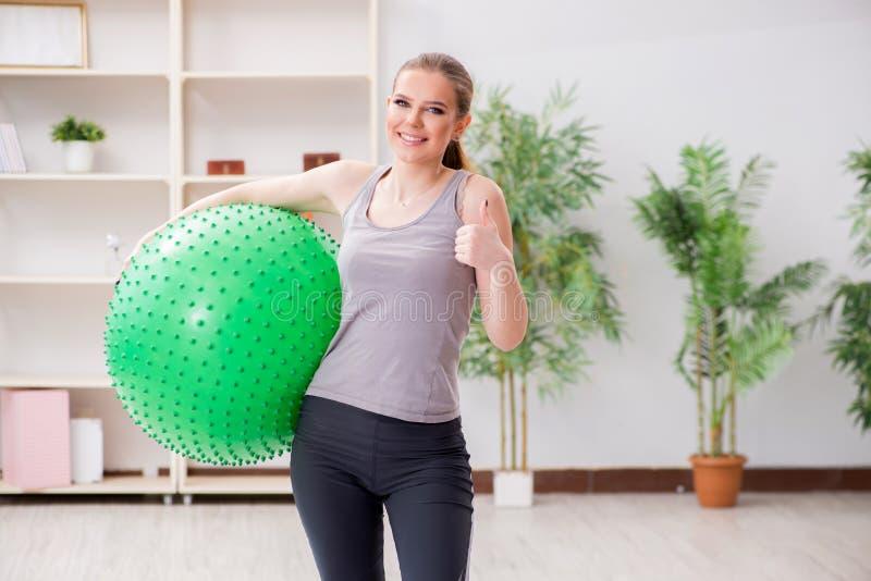 Die junge Frau, die mit Gymnastikball in der Turnhalle trainiert stockfotografie