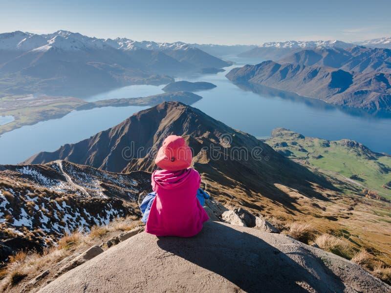 Die junge Frau, die am Rand der Klippe schauend über ausdehnender Ansicht von Bergen sitzen und die Seen von Roys ragen empor lizenzfreies stockbild