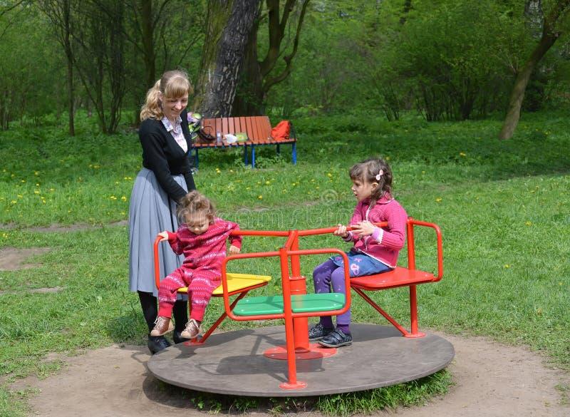 Die junge Frau rollt zwei Kinder auf einem Karussell im Park stockfotos