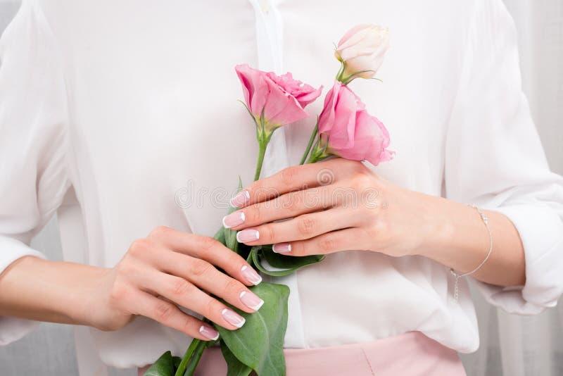 Die junge Frau, die schönen Eustoma hält, blüht in den Händen stockbilder