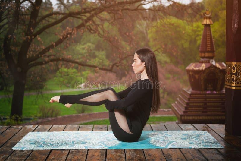 Die junge Frau, die Yoga tut, trainiert drau?en Yogameditation im Park stockbilder