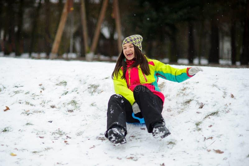 Die junge Frau zieht nett unten von einem Hügel auf dem Untertassenschlitten um stockbild