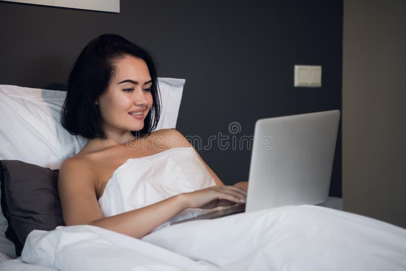 Die junge Frau zu Hause, die auf Bett sitzt, wachte Grasenlaptop auf lizenzfreie stockbilder