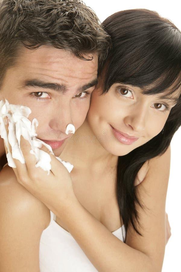 Die junge Frau, die zutrifft, Schaum rasierend, bemannt an Gesicht lizenzfreie stockfotos