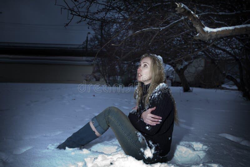 Die junge gefrorene Frau unter dem fallenden Schnee lizenzfreie stockfotos