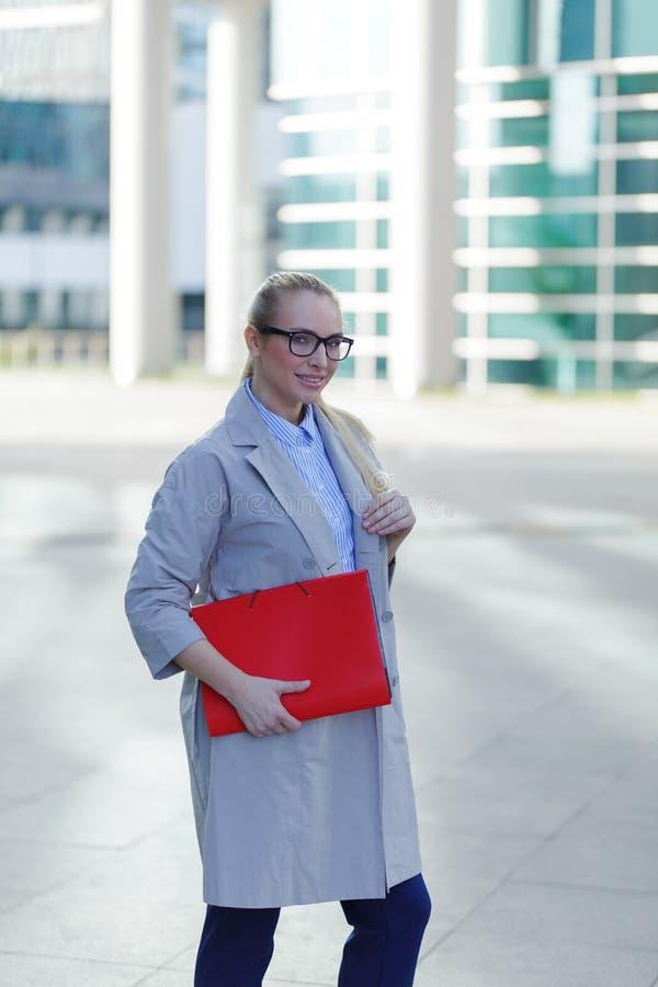 Die junge Geschäftsfrau hält in der Hand Ordner mit Dokumenten Gesch?ftsfraustellung nahe bei dem Gesch?ftszentrum lizenzfreies stockfoto
