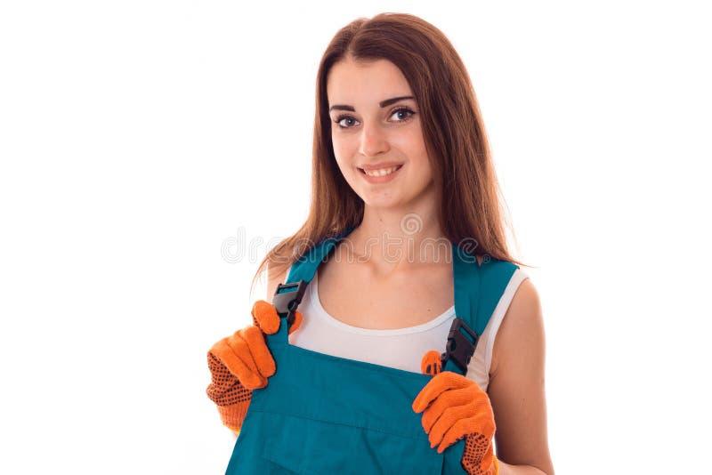 Die junge glückliche Brunettefrau in der Uniform macht renovationand lächelnd auf der Kamera, die auf weißem Hintergrund lokalisi stockbild