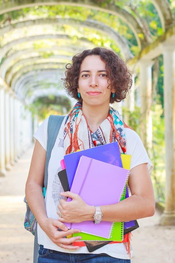 Die junge glückliche lächelnde Frau (Student, Lehrer) halten bucht stockbild