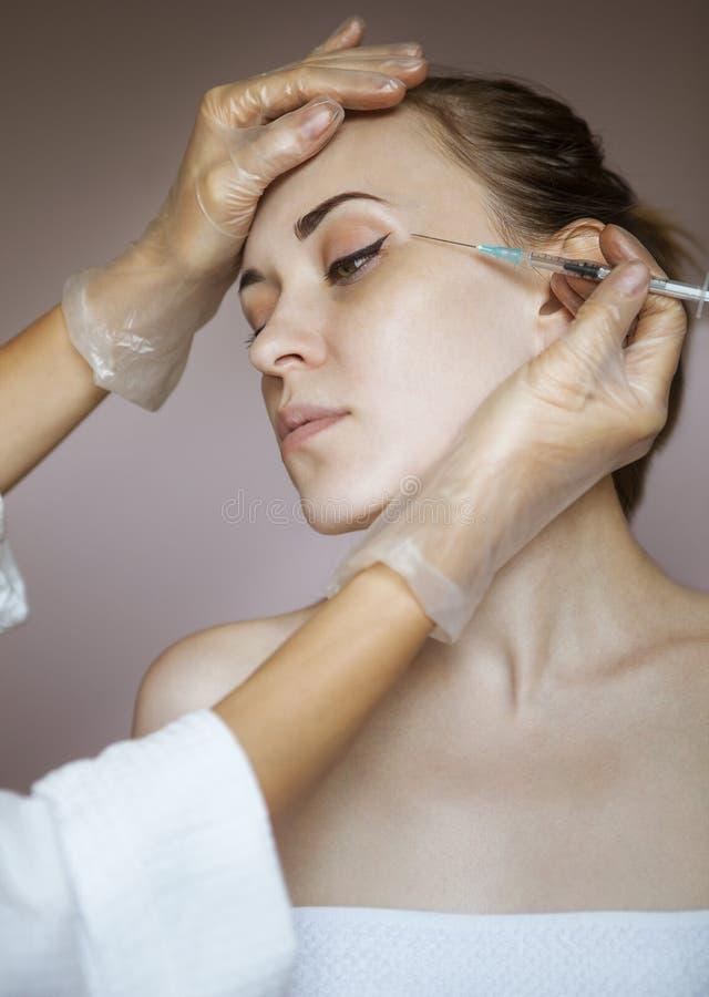 Die junge hübsche Frau, die kosmetische Einspritzung im Gesicht erhält, mögen a lizenzfreies stockbild