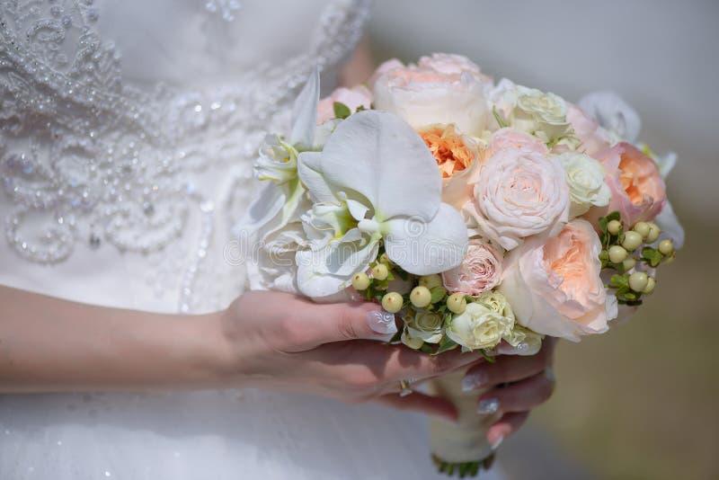 Die junge kaukasische Braut, die schönes verschönertes Kleid trägt und einen runden Pastell hält, färbte den Blumenstrauß, der gr stockfotos