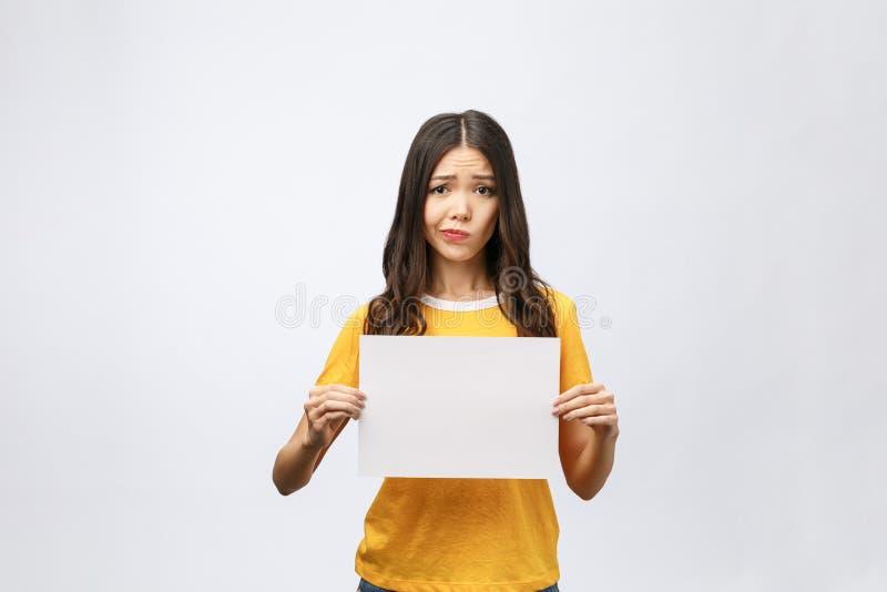 Die junge kaukasische Frau, die Blatt des leeren Papiers über lokalisiertem Hintergrund hält, betonte, entsetzt mit Schand- und Ü lizenzfreies stockbild