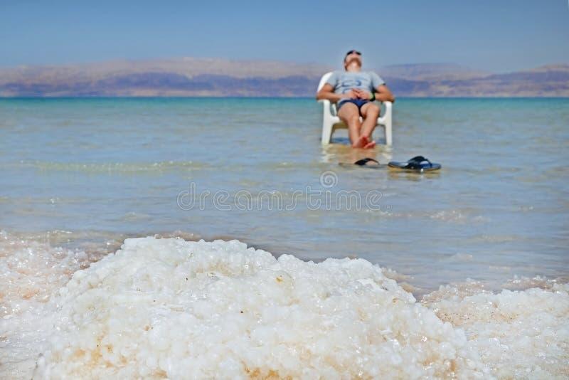 Die junge Kerlbrünette nimmt auf einem Stuhl im Toten Meer ein Sonnenbad Ansicht Jordan Mountainss von den Ufern des Toten Meers  stockbild