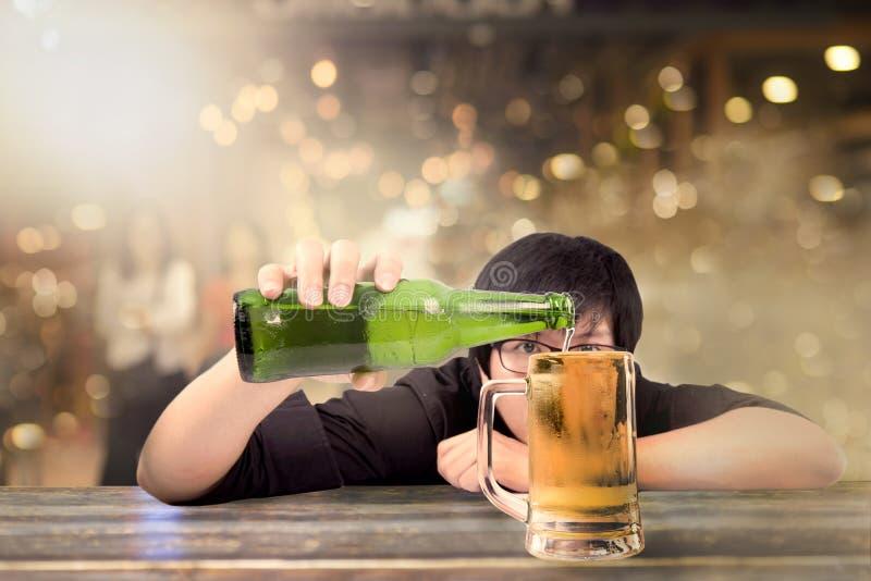 Die junge männliche Hand, die Bierflasche hält und füllen das Glas lizenzfreie stockfotos