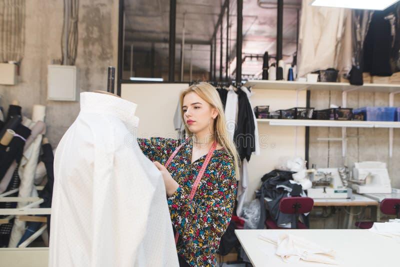 Die junge Näherin trägt Kleidung auf einer Attrappe Ein hübsches Mädchen stellt Kleidung in einem Modestudio her lizenzfreie stockfotos