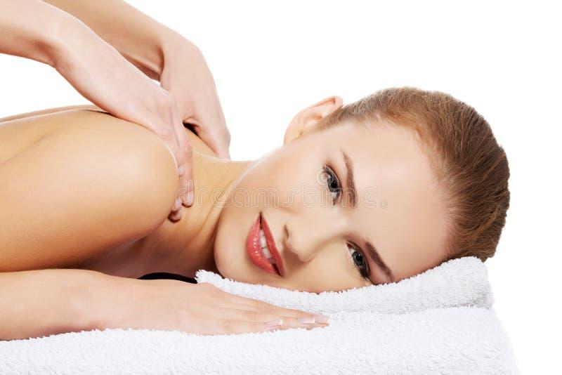 Die junge schöne kaukasische Frau, die auf einer Massagetabelle liegt und ist stockbilder
