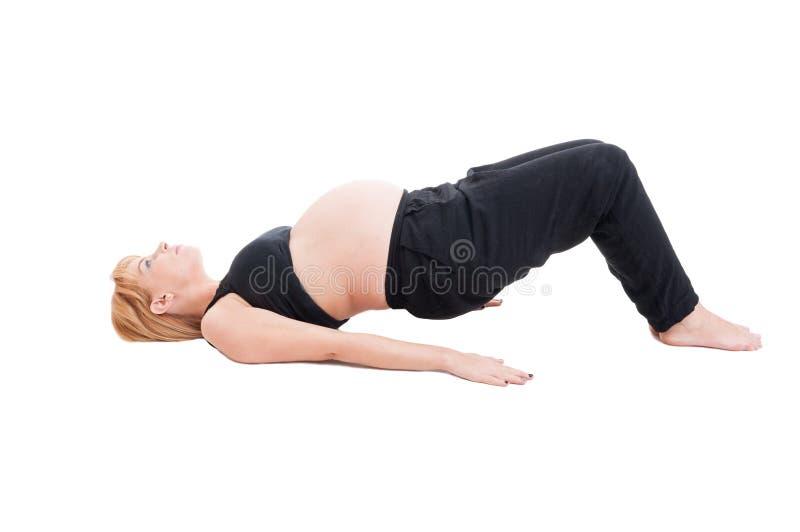 Die junge schöne schwangere Frau, die Sport macht, trainiert für Gesundheit stockfoto