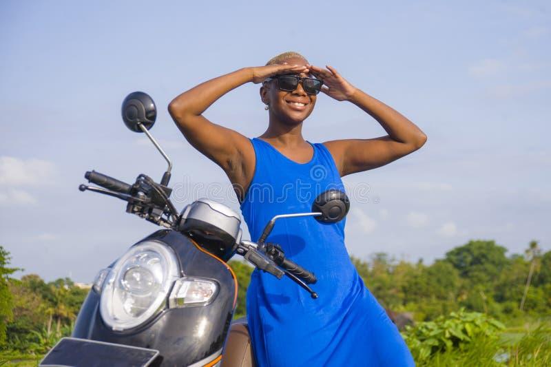 Die junge schöne und glückliche Aufstellung der schwarzen Frau des Afroamerikaners, die auf Rollermotorrad an der tropischen Land lizenzfreie stockfotografie