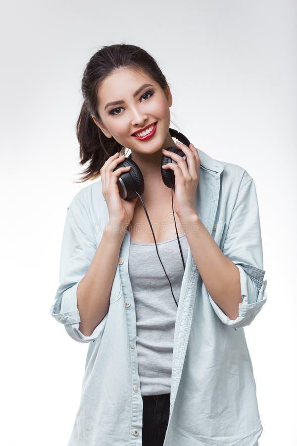 Die junge Schönheit, die große Kopfhörer hält, lokalisierte weißen Hintergrund lizenzfreie stockfotos