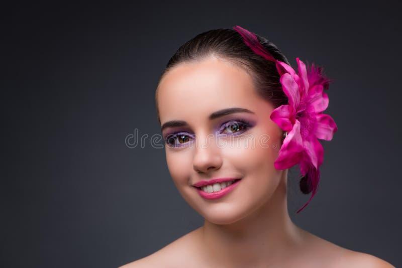 Die junge Schönheit mit Orchideenblume stockfotografie