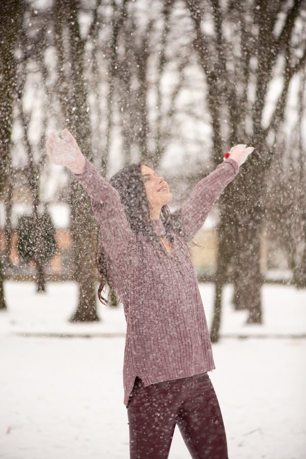 Die junge Sch?nheit genie?t den Schnee es in der Luft, in den positiven Gef?hlen, in der Freude und im Gl?ck zerstreuend Wintersp lizenzfreie stockfotografie