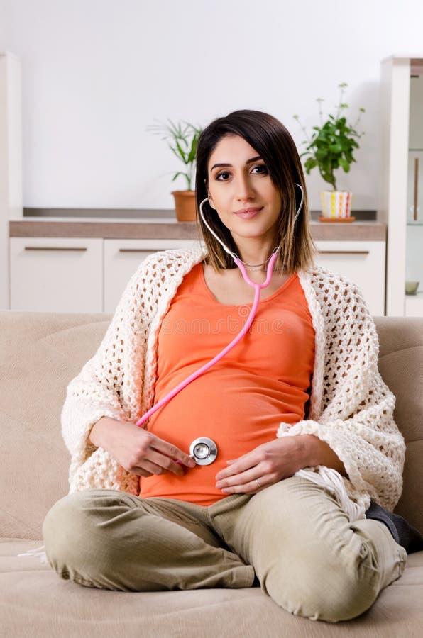 Die junge schwangere Frau zu Hause stockbild