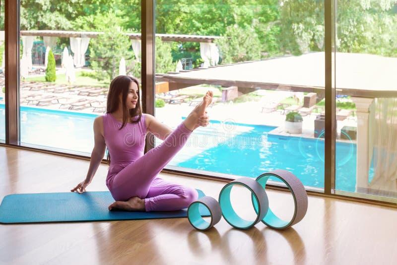 Die junge Sportlerin, die Yoga oder Eignung tut, trainiert mit Rad FO stockfoto