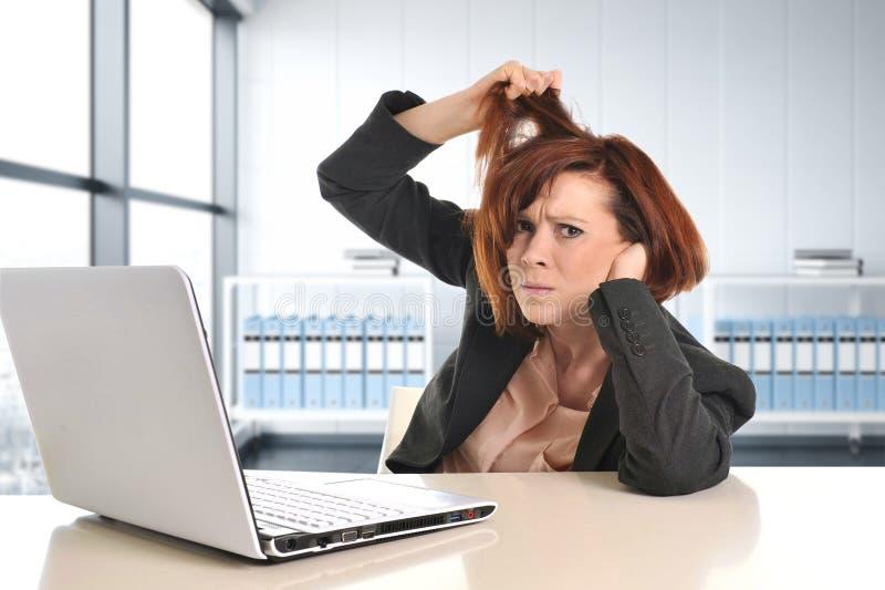 Die junge traurige und frustrierte Geschäftsfrau, die im Druck am modernen Bürofensterraum zieht ihr Haar arbeitet, ermüdete lizenzfreie stockfotografie