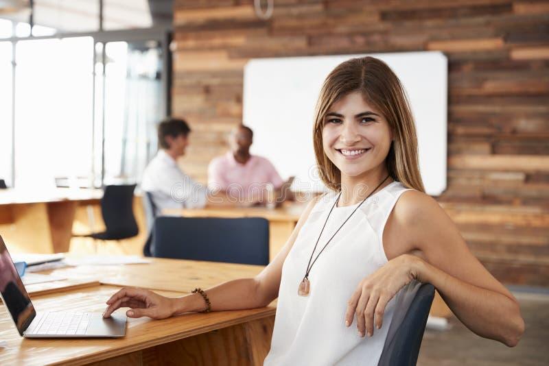 Die junge weiße Frau, die im kreativen Büro sitzt, schaut zur Kamera lizenzfreies stockbild