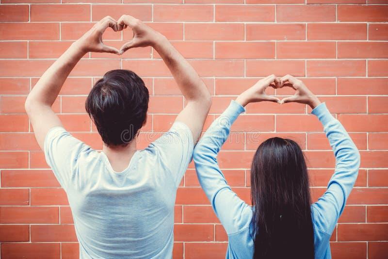 Die jungen asiatischen Paare, die in der Liebe mit Geste glücklich sind, übergeben Herzform lizenzfreie stockfotos