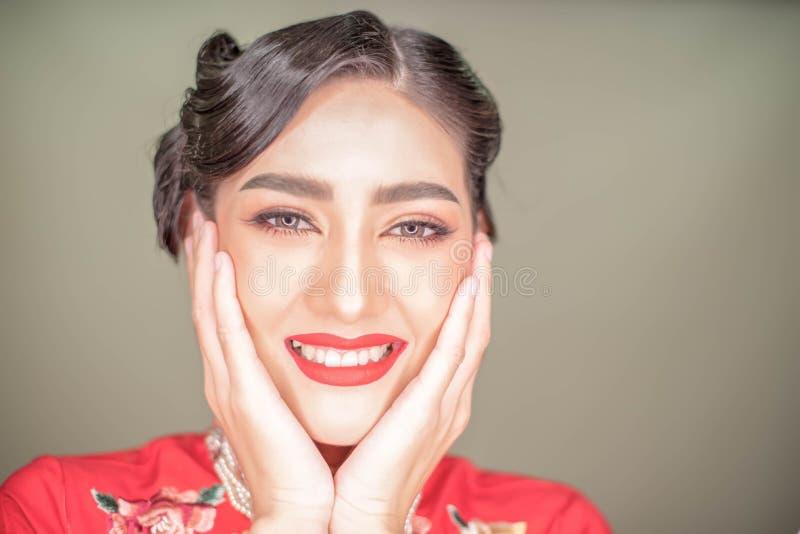Die jungen asiatischen Schönheiten im roten Kleid und im roten Lippenstift, Hände berühren ihr Gesicht lächelnd zur Kamera Schöne lizenzfreie stockbilder