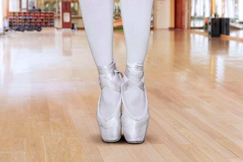 Die jungen Ballerinabeine, die mit stehen, gehen Haltung auf den Zehen stockfotografie