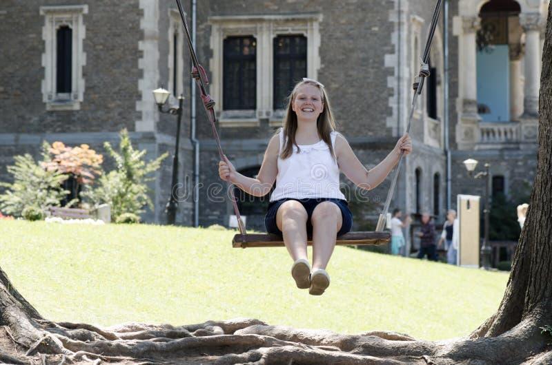 Die jungen Blondine, die auf hölzernem Schwingen nahe altem Schloss lächeln, übertreffen lizenzfreie stockfotografie
