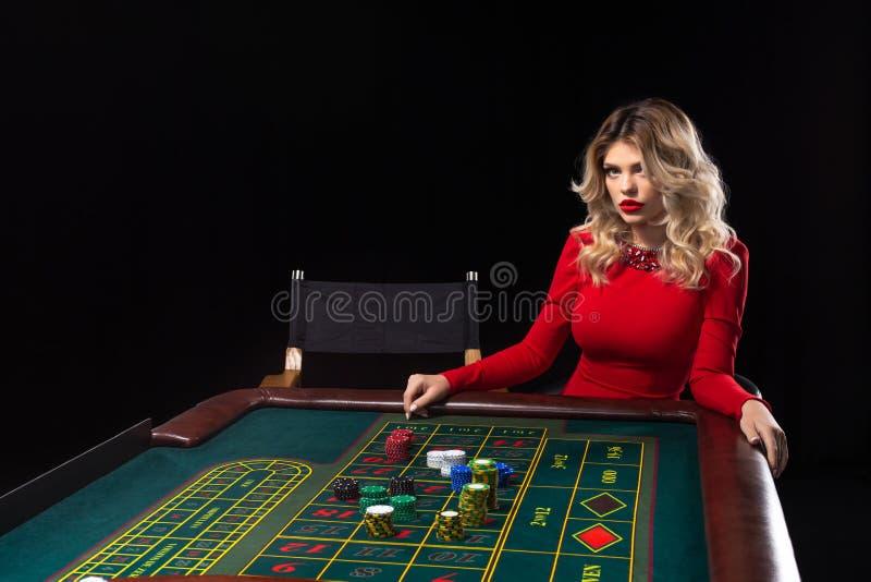 Die jungen Blondine, die schönes rotes Kleid tragen, spielen Roulette im Kasino lizenzfreie stockfotos