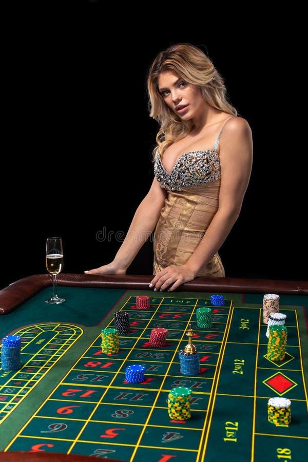 Die jungen Blondine, die schönes sexy glänzendes Kleid tragen, spielen Roulette im Kasino stockfotografie