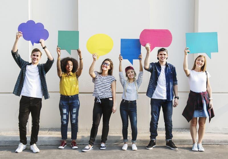 Die jungen erwachsenen Freunde, die copyspace halten, bekleben Gedankenblasen mit Plakaten stockfoto