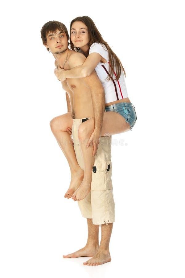 Die jungen glücklichen Paare, die zusammen spielen, tragen huckepack lizenzfreie stockfotografie