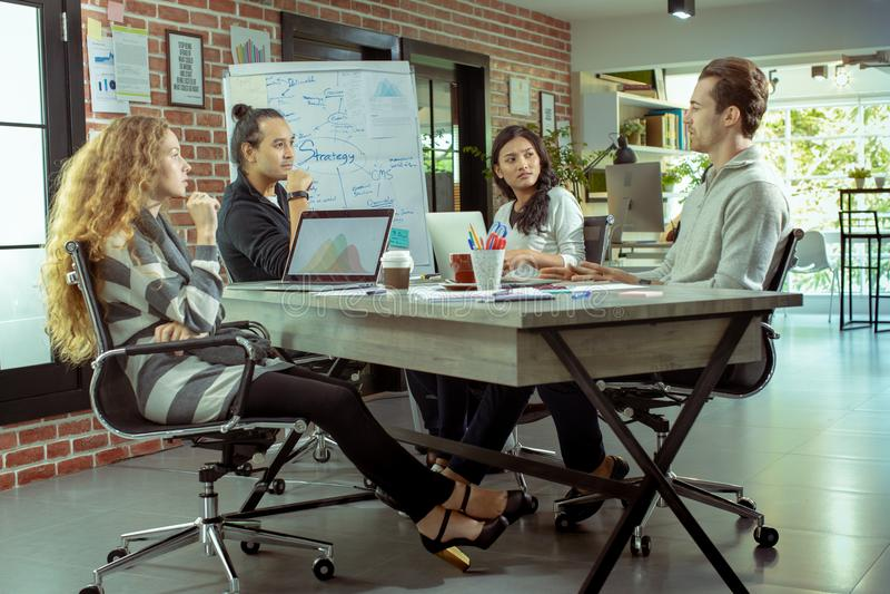 Die jungen kaukasischen und asiatischen Geschäftsmänner treffen das Team stockfotografie