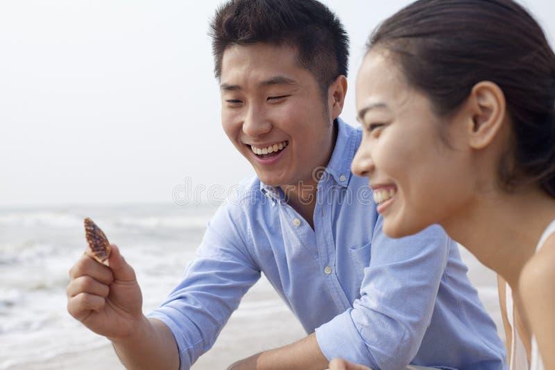 Die jungen lachenden Paare, die Muschel auf das Wasser betrachten, umranden, China stockfotografie