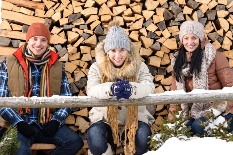 Die jungen Leute, die außerhalb des Winters sitzen, kleiden Holz lizenzfreie stockbilder