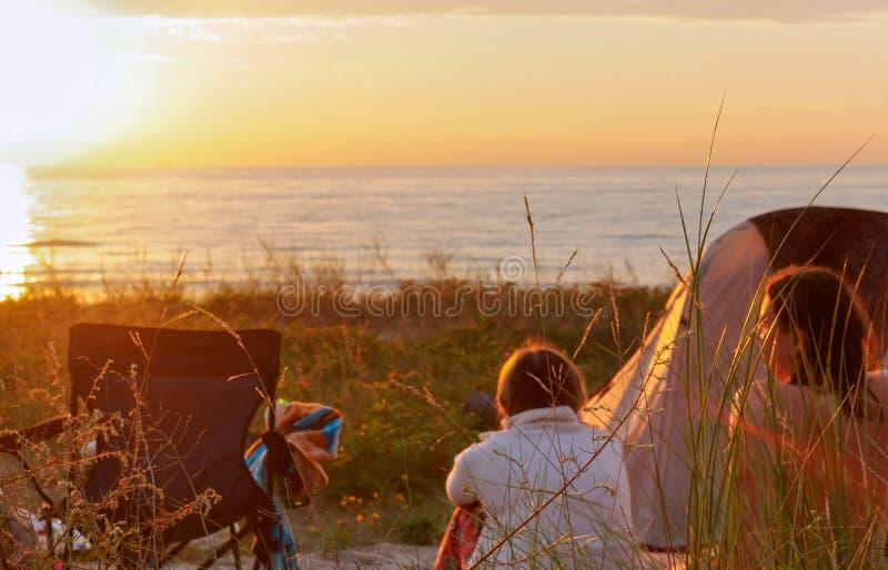 Die jungen Leute nahe dem Zelt auf dem Strand, dem Mädchen und dem Jungen, die den Sonnenuntergang bewundern lizenzfreie stockfotos