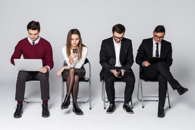 Die jungen Leute sitzen in Folge im Geschäftszentrum beim Warten auf das Interview lokalisiert auf Weiß stockfotografie