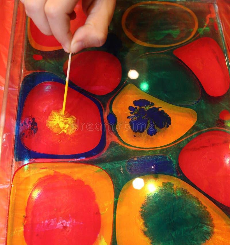 Die Jungen mading eine helle Malerei mit Farben stockfotos