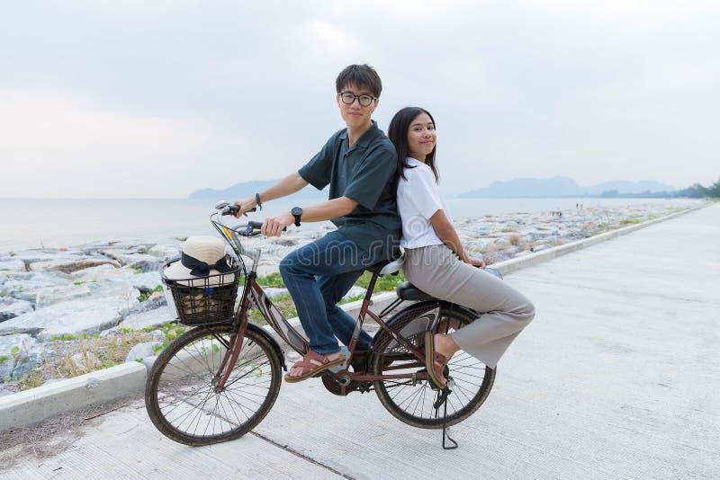 Die jungen netten asiatischen Paare sitzen auf einem Fahrrad zusammen lizenzfreie stockfotografie