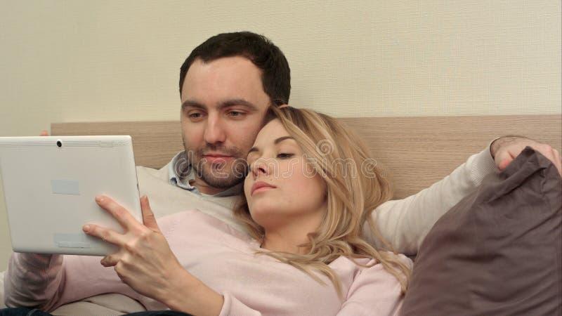 Die jungen Paare, die auf dem Bett liegen, machen den Einkauf über dem Internet unter Verwendung der Tablette unter Verwendung de stockfotos