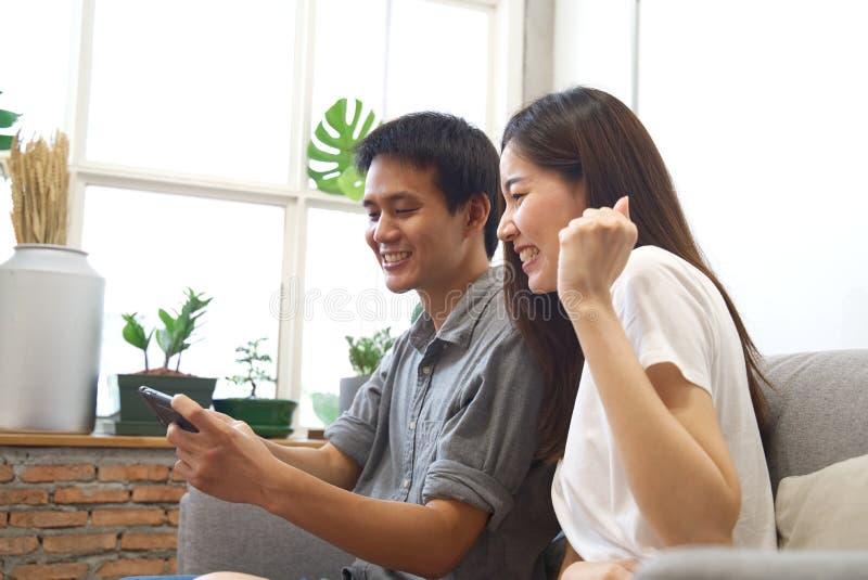 Die jungen Paare, die auf Sofa sitzen, passen Handy auf und fühlen sich surprise&happy, wenn das Ergebnis mit Lächelngesicht kenn lizenzfreies stockfoto