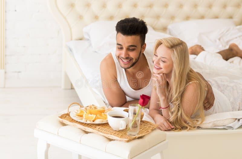 Die jungen Paare, die im Bett liegen, essen Frühstücks-Morgen mit roter Rose Flower, glückliches Lächeln-hispanischem Mann und Fr lizenzfreie stockfotos