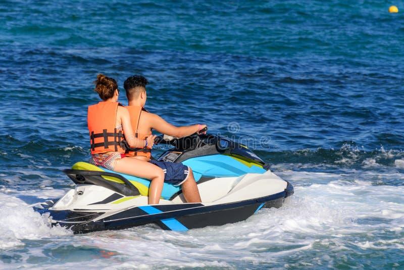Die jungen Paare, die einen Jet reiten, fahren im karibischen Meer Ski und tragen Sicherheitsjacken Riviera-Maya, Mexiko stockfotografie