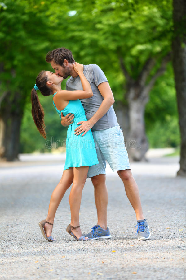 Die jungen Paarliebhaber in der Liebe küssend im Sommer parken lizenzfreie stockfotos