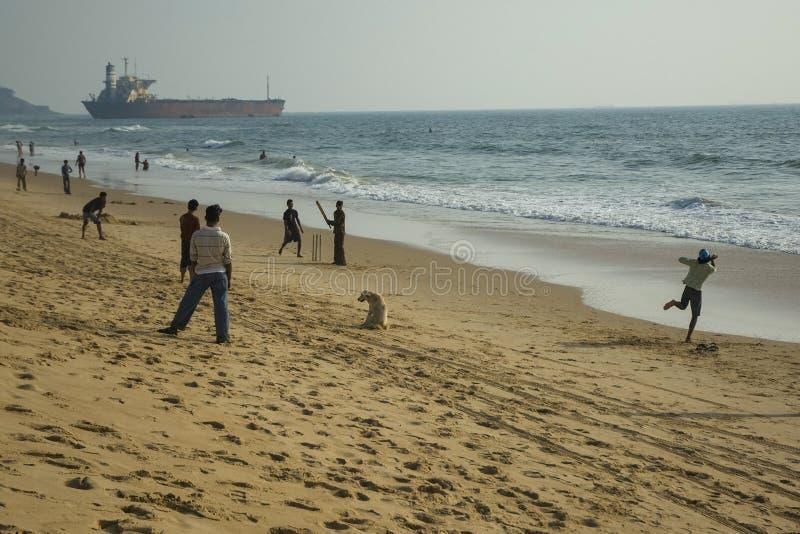 Die Jungen spielen Kricket auf dem Indischen Ozean auf Candolim-Strand Indien, Goa - 27. Januar 2009 stockbild